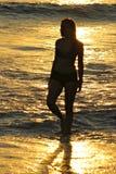 女孩在日落的海洋 免版税库存照片
