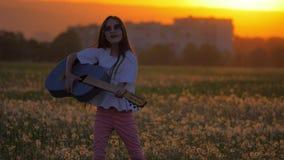 女孩在日落,跳舞和演奏吉他身分期间的少年太阳镜在房子附近的一个领域 概念庆祝 股票视频