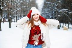 女孩在时髦的冬天在背景的一个公园给休息穿衣 免版税图库摄影