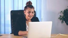女孩在时髦的衣裳打扮,坐在办公室和打印信息在膝上型计算机 股票录像