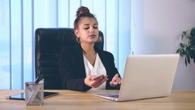 女孩在时髦的衣裳打扮,坐在办公室和打印信息在膝上型计算机 股票视频