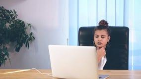 女孩在时髦的衣裳打扮,坐在办公室和打印信息在膝上型计算机 影视素材