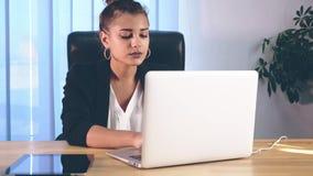 女孩在时髦的衣裳打扮,坐在办公室和打印记录片 股票录像