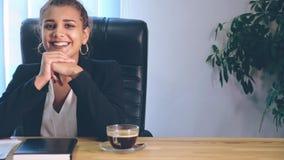 女孩在时髦的衣裳打扮,坐在办公室 在这时间她真诚地微笑 影视素材