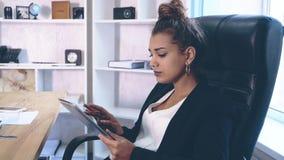 女孩在时髦的衣裳打扮,坐在办公室 股票视频