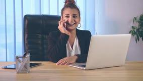 女孩在时髦的衣裳打扮,坐在膝上型计算机附近的办公室 在这时间,她由电话讲话 影视素材