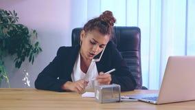 女孩在时髦的衣裳打扮,坐在膝上型计算机附近的办公室 股票录像