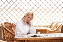 女孩在明亮的温暖的大气的早晨咖啡 库存图片