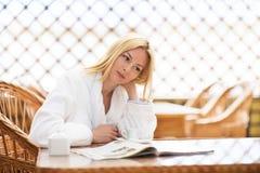 女孩在明亮的温暖的大气的早晨咖啡 免版税库存图片