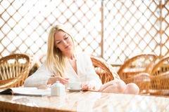 女孩在明亮的温暖的大气的早晨咖啡 库存照片