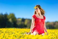 女孩在一个花草甸的春天用蒲公英 免版税库存照片