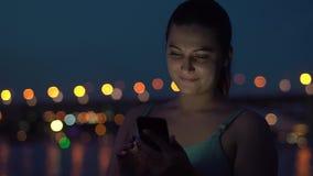 女孩在晚上使用一sartphone以城市为背景 股票录像