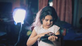 女孩在晚上在一种片剂读社会媒介岗位在屋子里户内 孩子和互联网生活方式 股票录像
