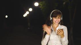女孩在晚上走在城市公园由灯笼光  耳机的美女听到在她的音乐 影视素材