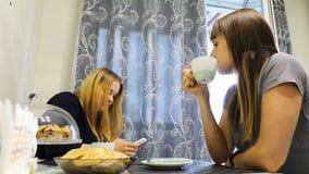 女孩在智能手机坐在饭桌上并且写消息 影视素材
