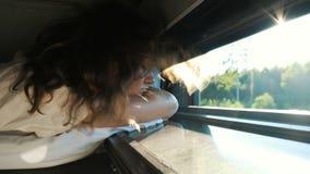 女孩在有一个开窗口的一列火车睡觉在日落,风吹她的头发,太阳的光芒通过树淡光 股票录像