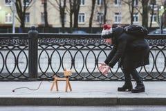 女孩在有一条虚构的狗的街道上使用,实际上是灯 免版税库存图片