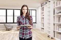 女孩在有两个窗口的一个家庭书库里 免版税图库摄影