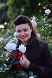 女孩在有两朵玫瑰的(画象白玫瑰庭院里 图库摄影