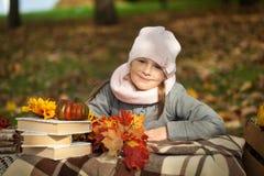 女孩在有书、花束和一点南瓜的秋天公园 免版税库存图片