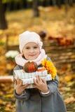 女孩在有书和一点南瓜的秋天公园 图库摄影