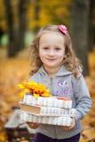 女孩在有书和一点南瓜的秋天公园 免版税库存照片