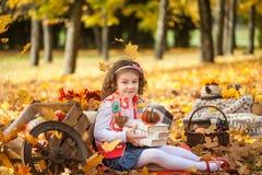 女孩在有书和一点南瓜的秋天公园 库存照片