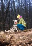 女孩在有她多壳的狗的森林里 免版税库存照片