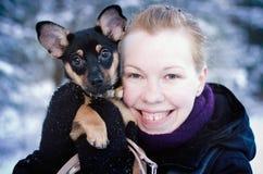 女孩在有她的狗的冬天森林里 免版税库存照片