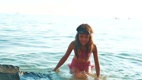 女孩在有岩石和石头的海沐浴 女孩青少年的女儿在海洋的波浪的水中游泳 股票视频