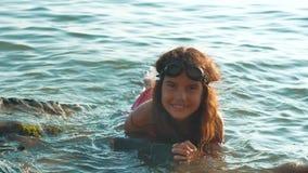女孩在有岩石和石头的海沐浴 女孩青少年的女儿在海洋的波浪的水中游泳 影视素材