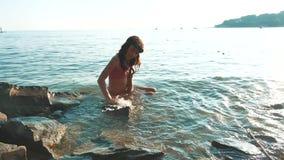 女孩在有岩石和石头的海沐浴 女孩青少年的女儿在生活方式的水中游泳波浪  影视素材