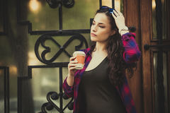 女孩在有智能手机和外带的咖啡的城市 库存图片