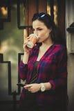 女孩在有智能手机和外带的咖啡的城市 库存照片