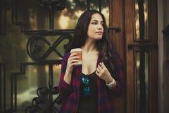 女孩在有智能手机和外带的咖啡的城市 图库摄影