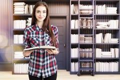 女孩在有梯子的一个家庭书库里,黑 库存照片