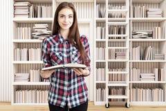 女孩在有梯子的一个家庭书库里 免版税库存图片