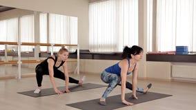 女孩在有氧类执行锻炼与微笑 健身辅导员工作与健身房的一个女孩 股票视频