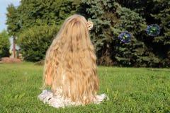 女孩在有泡影的公园 库存照片