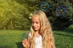 女孩在有泡影的公园 免版税图库摄影