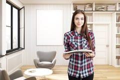 女孩在有灰色扶手椅子的一个家庭书库里 免版税库存图片