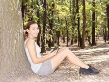 女孩在有片剂计算机的公园 免版税库存照片