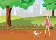 女孩在有狮子狗的公园走 免版税库存图片