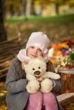 女孩在有玩具熊的秋天公园 免版税库存照片