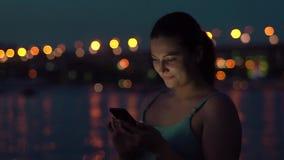 女孩在有的晚上使用一个智能手机,当走在城市附近一种好心情时 股票视频