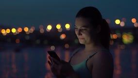 女孩在有的晚上使用一个智能手机,当走在城市附近一种好心情时 HD 股票视频