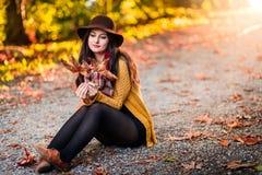 女孩在有秋叶的一个公园在她附近 免版税库存照片