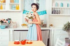 女孩在有花的厨房里 免版税库存照片