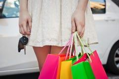 女孩在有袋子的一辆白色汽车附近站立,做购物 免版税库存图片