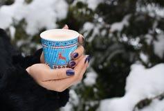 女孩在有雪的冷的冬天森林里拿着咖啡 免版税库存图片